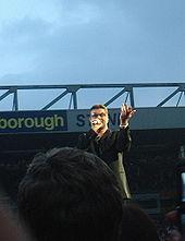 George Michael, met op de achtergrond de Norwich en Peterborough Stand, in juni 2007.