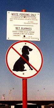 Bordje bij een strand met de tekst 'zwarten en honden zijn niet toegestaan'.