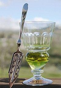 Sklenice naplněná přírodně zbarvenou verte. Vedle ní je lžička absintu.