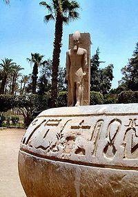Hieroglyphen auf Stein; dahinter die Statue von Ramses II