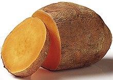 Eine Süßkartoffel mit einer abgeschnittenen Scheibe.