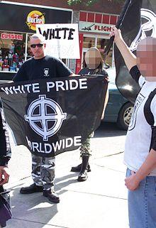 """Vaandel omhoog gehouden door een persoon op een """"White Pride"""" bijeenkomst in Calgary, Canada"""