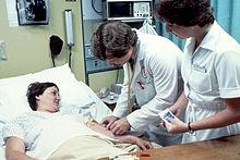 1980年,医生带着护士在医院进行验血。