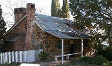 """Een huisje van """"uitgeklede"""" steen met stenen schoorstenen in Australië"""