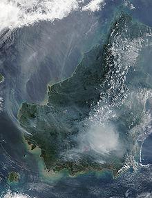 Satellietbeeld van het eiland Borneo op 19 augustus 2002, waarop de rook van brandende veenmoerasbossen te zien is