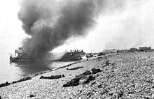 Vernietigde landingsvaartuig in brand met Canadese doden op het strand. Een betonnen kanonopstelling aan de rechterkant bedekt het hele strand. Het steile strand is duidelijk te zien.