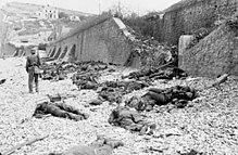 Canadese doden op het blauwe strand van Puys. Gevangen tussen het strand en de hoge zeewering (versterkt met prikkeldraad), maakten ze makkelijke doelen voor MG34 machinegeweren in een Duitse bunker. De bunkervuurspleet is in de verte zichtbaar, net boven het hoofd van de Duitse soldaat.