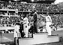 Jesse Owens op het podium na het winnen van het verspringen op de Olympische Zomerspelen van 1936.