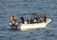 Verdachte piraten houden hun handen omhoog.