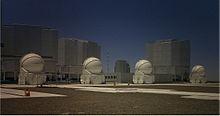 De vier AT's in Paranal. De Unit Telescopen staan op de achtergrond
