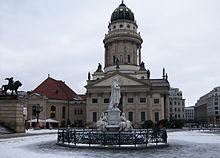 Französischer Dom in de winter van 2009: de koepeltoren aan de rechterkant en het roodkapte eigenlijke kerkgebouw aan de linkerkant, het marmeren monument voor Friedrich Schiller op de voorgrond.