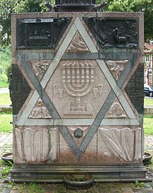 Der Davidstern und der siebenarmige Kerzenhalter (Menora) sind Symbole der Juden und des Judentums. Der Würfel auf diesem Bild steht an der Stelle einer alten Synagoge. Er wurde zur Erinnerung an den Holocaust geschaffen.