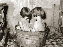 Twee kinderen badend in een kleine metalen badkuip