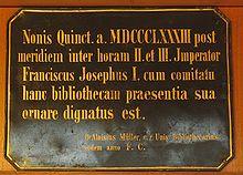 """Das lateinische Wort auf dieser Tafel lautet: """"Im Jahre 1883 nach Mittag in der zweiten und dritten Stunde beehrte Kaiser Franz Joseph mit einer Gruppe von Leuten diese Bibliothek mit seiner Anwesenheit."""