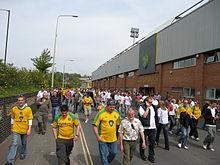 Fans die langs de weg lopen waarna het stadion zijn naam krijgt