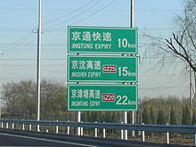 """Straßenschild auf einer chinesischen Autobahn in der Nähe von Peking. Das Schild verwendet das internationale Symbol """"km"""" für """"Kilometer""""."""