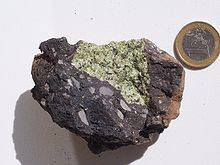 Перидотитовый (зеленый) мантийный ксенолит в (темной) вулканической бомбе из Вулкан-Эйфеля, Германия. Одна монета евро по шкале