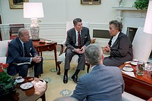 Reagan a George Shultz jednají v Oválné pracovně s premiérem Dominiky Eugenií Charlesem o událostech v Grenadě, listopad 1983.