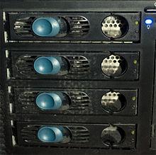 Detail 4 disků, které tvoří pole RAID, zabudované do stolního systému. Modré západky umožňují výměnu disků za chodu systému.