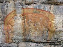 Een Regenboogslang geschilderd op een grotwand door Aboriginal kunstenaars.
