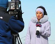 Ein Fernsehreporter, der ein Mikrofon hält.