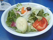 Bord met groene salade, ui, tomaat, komkommer, wortel en een zwarte olijf