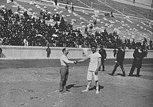 Carl Schuhmann (links) en Georgios Tsitas schudden elkaar de hand voor de laatste wedstrijd van de worstelcompetitie.