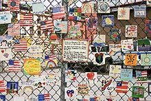Serie handgeschilderde tegels, opgedragen aan de slachtoffers van de aanslagen van 11 september, op het hek van een autotuin in New York City.