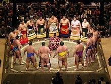 Sumo-Kämpfer umkreisen den Schiedsrichter in der Eröffnungszeremonie.