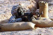 Een soldaat in Syrië, met een AK-47 geweer en een gasmasker