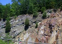 De bovenste schuine laag van grijs dolomiet is ongeveer 500 miljoen jaar oud. De roodachtige rhyoliet waarop het dolomiet rust, is ongeveer 1,5 miljard jaar oud. Er ontbreekt een miljard jaar geologische geschiedenis op deze foto. Missouri Ozarks.