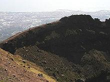 Een blik op de kratermuur van de Vesuvius, met op de achtergrond de stad Torre del Greco
