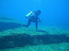 Ein Taucher, der auf dem gigantischen Yonaguni-Felsen unter Wasser geht.