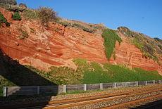 Levendige Nieuwe Rode Zandsteen, Triasperiode. Het toont gekruiste duinzandsteen gevormd in een woestijn. Devon, bij de monding van de rivier Exe