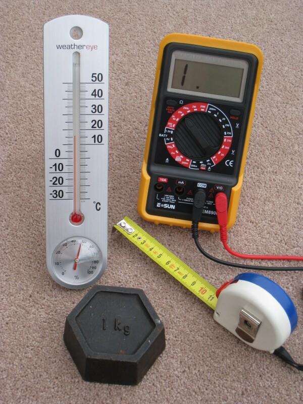 Vier alltägliche Messgeräte mit metrischer Kalibrierung: ein in Zentimetern geeichtes Maßband, ein in Grad Celsius geeichtes Thermometer, ein Kilogramm Gewicht und ein elektrisches Multimeter, das Volt, Ampere und Ohm misst.