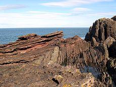 Siccar Point, geërodeerde zacht glooiende lagen Devoon Oud Rood Zandsteen die een afdekking vormen over een conglomeraatlaag en oudere verticaal bedekte Silurische grijsacke gesteenten.