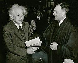 新入籍的阿尔伯特-爱因斯坦从菲利普-福曼法官手中接过美国公民证书。