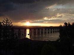 In de schemering. Een van de stronken van de oorspronkelijke brug tekent zich af tegen de zonverlichte Firth.