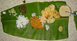 Mittagessen aus Südindien, serviert auf einem Wegerichblatt. Siehe Bild für ausführliche Beschreibungen.