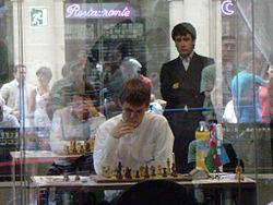 Teimour Radjabov kijkt van een afstand naar zijn rivaal Magnus Carlsen.