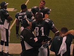 Owens (81) met de Eagles in gesprek met een coach.
