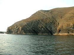 Schichten sind die Gesteinsschichten, die ursprünglich horizontal abgelagert wurden. Dies stammt aus Trwyn y Fulfran, Lleyn, Wales.