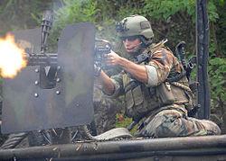 US Navy Boat Team bemanningslid die een zwaar machinegeweer afvuurt. Let op verdedigend pantser en muntriem; gebruikte patronen vallen. Bemanningslid in gecamoufleerde outfit, radioapparatuur, camera op helm, machinepistool over zijn schouder.