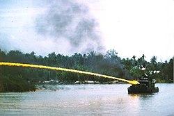 Rivierboot van de Amerikaanse Brownwater Navy die een brandende mix van napalm van een vlammenwerper in Vietnam schiet.