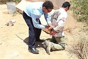 Een Iraakse politieagent houdt een verdachte aan tijdens een trainingsoefening
