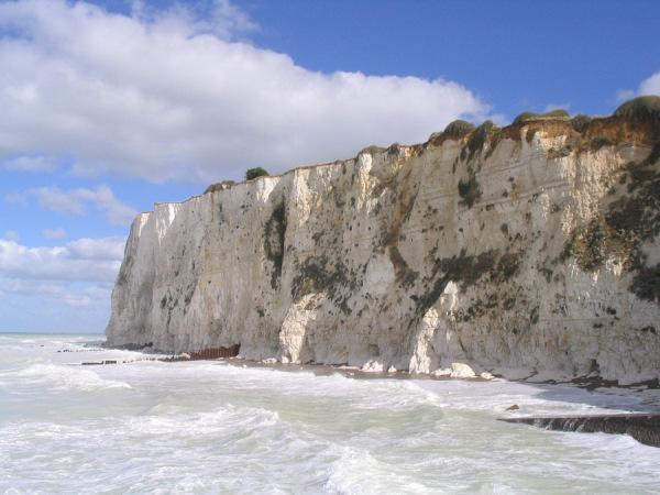 Kreidefelsen von Mers-les-Bains, bei Flut. Man kann gerade noch schräge dunkle Linien auf der Kreide sehen: diese werden von Linien aus Feuerstein, dem einzigen anderen Bestandteil der Kreide, gebildet.