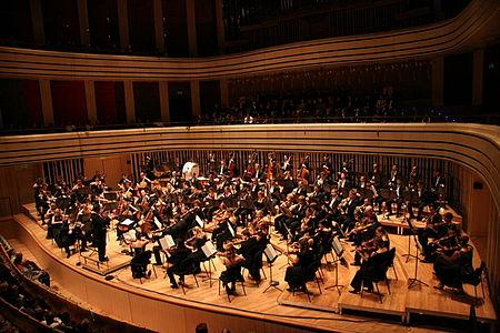 Auftritt des Dohnanyi-Orchesters. Der Dirigent dieses Orchesters hat die zweiten Violinen zu seiner Rechten. Die Kontrabässe befinden sich nach dem deutschen Grundriss auf der Rückseite