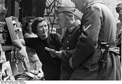 Dit is een veel complexere vorm van interactie. Duitse soldaten praten met een Franse vrouw in Lotharingen, Frankrijk, november 1940.