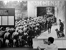 Vrouwelijke gevangenen gaan de Siemens-fabriek binnen om slavenarbeid te verrichten, met SS-bewakers in de buurt