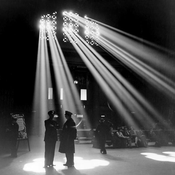 Lichtstrahlen scheinen durch Metallmuster in einen Bahnhof